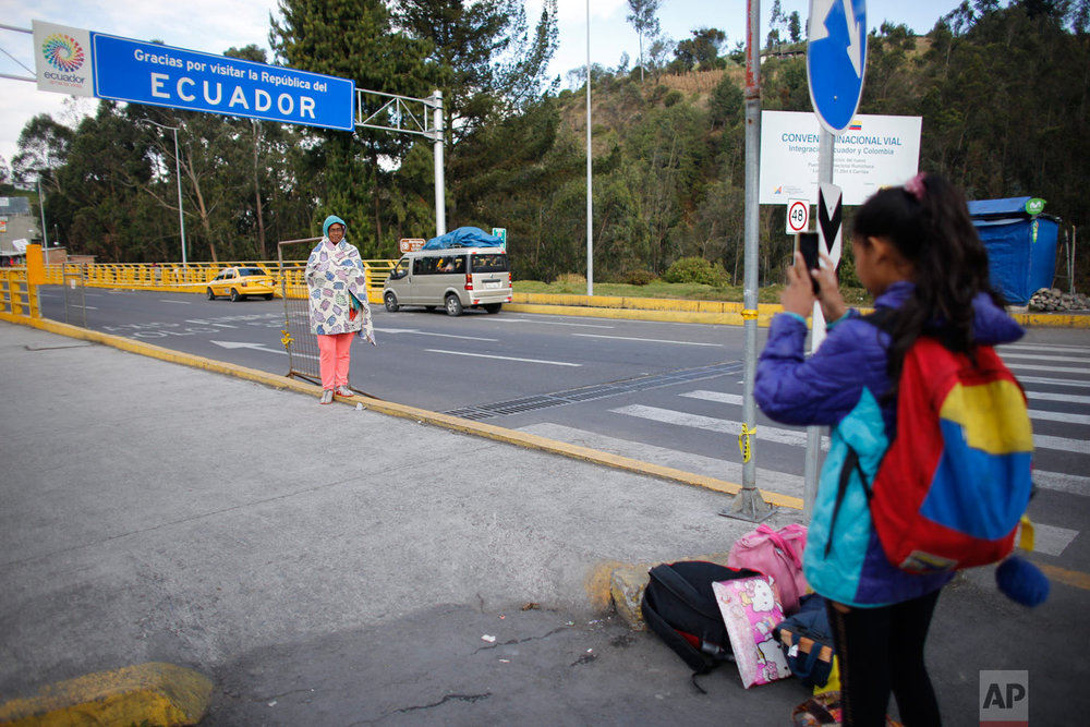 In this Sept. 5, 2018 photo, 10-year-old Venezuelan Angelis takes a picture of her mother Sandra Cadiz after they crossed the Colombian border into Huaquillas, Ecuador, as they journey to Peru. In total they had to go through three separate migration lines, but eventually, they were let through into Ecuador. (AP Photo/Ariana Cubillos)
