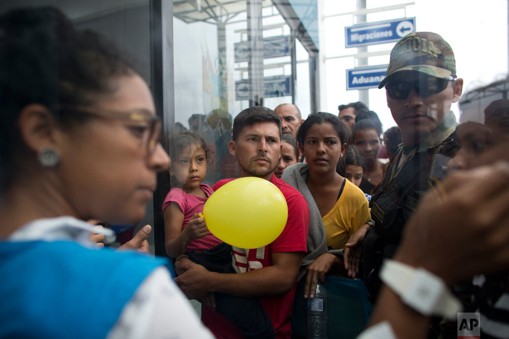In this Sept. 6, 2018 photo, Venezuelans wait in line to be attended by Peruvian immigration officials in hopes of entering the country, in Tumbes, Peru. Many Venezuelans' final destination is Lima, Peru, a city where most believe they will have more opportunities than in Colombia or Ecuador, the countries they must pass along the way. (AP Photo/Ariana Cubillos)