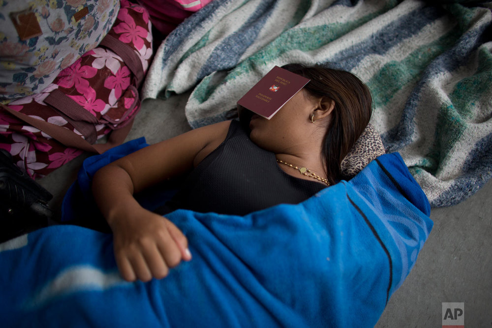 """In this Sept. 7, 2018 photo, a Venezuelan woman covers her eyes with a Peruvian """"health"""" passport to get some sleep near the Peruvian immigration office in Tumbes, Peru. At the border, Peruvian immigration authorities give foreigners a """"Health Passport"""" after they pass a health check-up.(AP Photo/Ariana Cubillos)"""