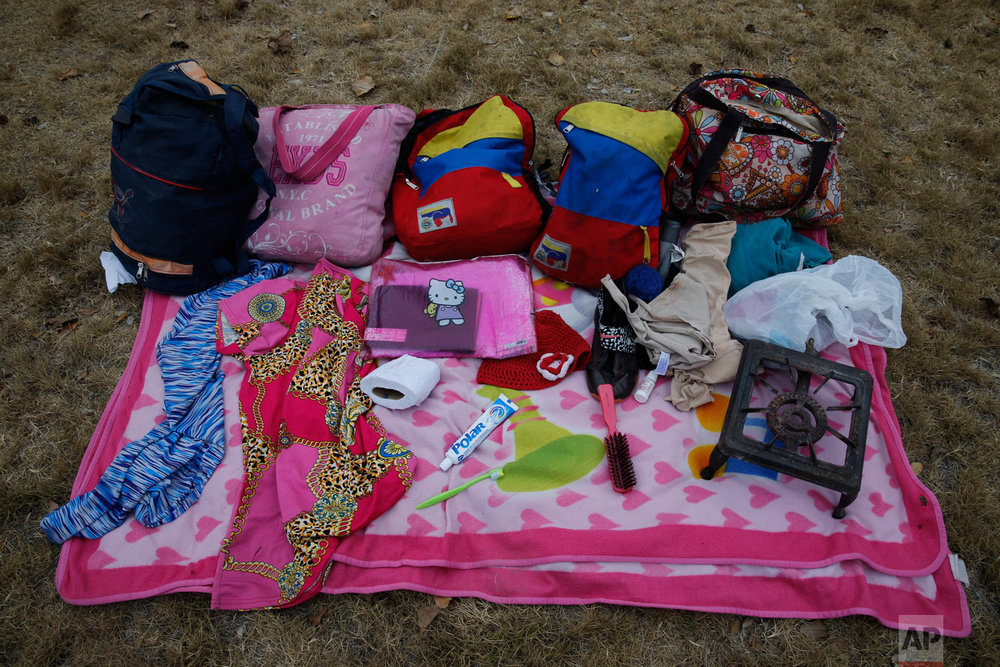 In this Sept. 7, 2018 photo, the belongings of Venezuelan mother Sandra Cadiz and her 10-year-old daughter Angelis, which they carried by foot on their journey from Venezuela to Peru, sit neatly displayed for a picture in Huaquillas, Ecuador. They carried old clothes, shoes, a brush with bristles bent in opposing directions and a smashed roll of toilet paper. There was also an old, heavy iron gas burner Cadiz's a sister had insisted she deliver to a niece in Lima. (AP Photo/Ariana Cubillos)