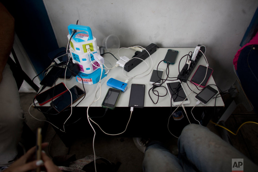 In this photo Sept. 7, 2018 photo, cellphones belonging to Venezuelans are charged for free at the immigration office in Aguas Verdes, Peru.It's not known how many reach their final destination. Facebook groups are filled with posts from Venezuelans looking for friends and family members who took off walking and disappeared. (AP Photo/Ariana Cubillos)