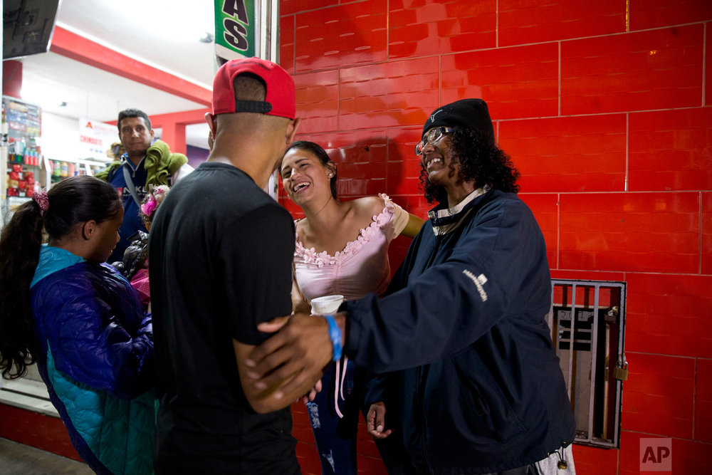 In this Sept. 8, 2018 photo, Sandra Cadiz, right, smiles as she reunites with her son Leonardo, front left, and her daughter-in-law Daniela Gomez, as she and her 10-year-old daughter Angelis, far left, arrive to the bus station in Lima, Peru, after their long trip from Venezuela. Cadiz immediately noticed that her son and his family looked like they'd gained weight. Angelis, meanwhile, admired her baby niece's sparkling new shoes. (AP Photo/Ariana Cubillos)