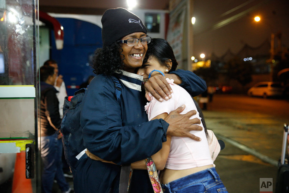 In this Sept. 8, 2018, Venezuelan Sandra Cadiz, left, embraces her daughter-in-law Daniela Gomez as she arrives at the bus station in Lima, Peru, her final destination after leaving Venezuela. Cadiz spent all but her last six dollars on the bus tickets, getting her and her daughter seats overlooking Peru's desert terrains in the 18-hour ride to the capital. (AP Photo/Ariana Cubillos)