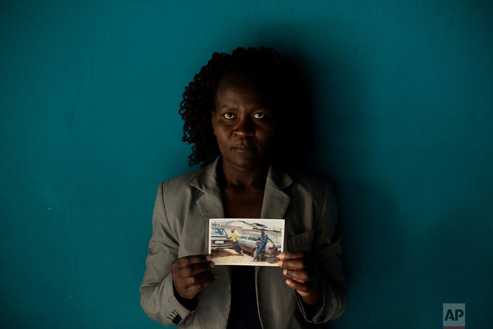In this Friday, Aug. 24, 2018 photo, Zimbabwean migrant Banele Nkomo holds a photograph of her missing brother, Francis, in Johannesburg. (AP Photo/Bram Janssen)
