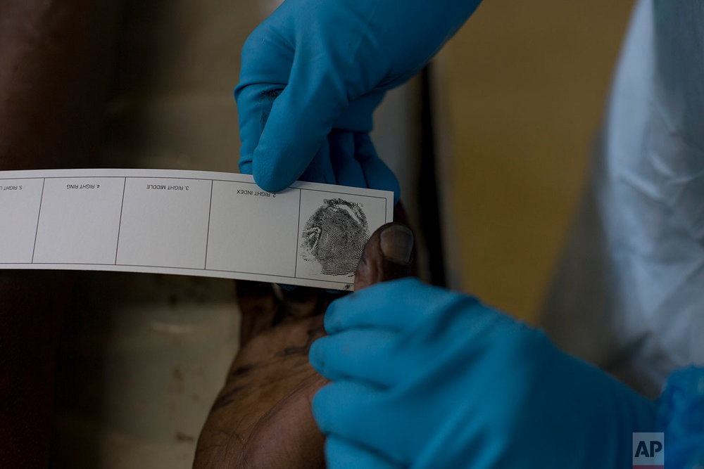 In this Wednesday, April 18, 2018 photo, a pathologist takes a fingerprint of an unidentified male for forensic examination at a mortuary in Johannesburg. (AP Photo/Bram Janssen)