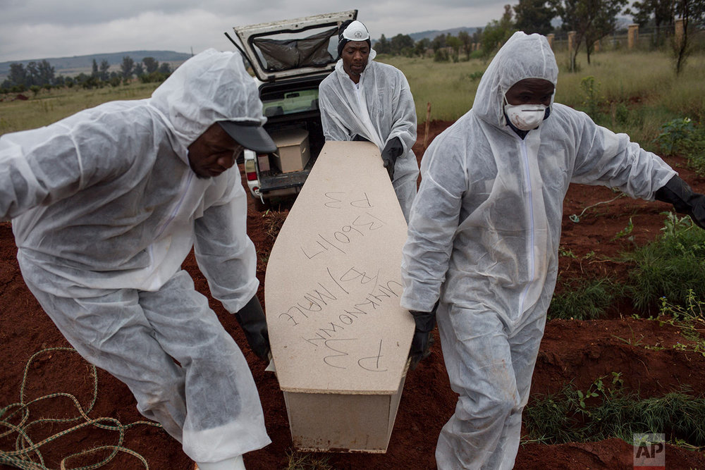 In this Thursday, April 12, 2018 photo, mortuary workers bury the coffin of an unidentified male at Olifantsvlei cemetery outside Johannesburg. (AP Photo/Bram Janssen)