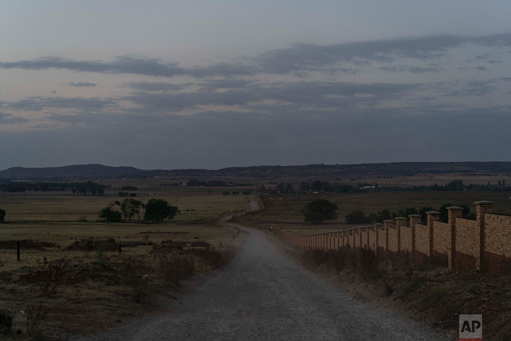 """This Wednesday, Oct. 3, 2018 photo shows the road leading to the Olifantsvlei cemetery outside Johannesburg where bodies are buried in """"pauper"""" graves. (AP Photo/Bram Janssen)"""