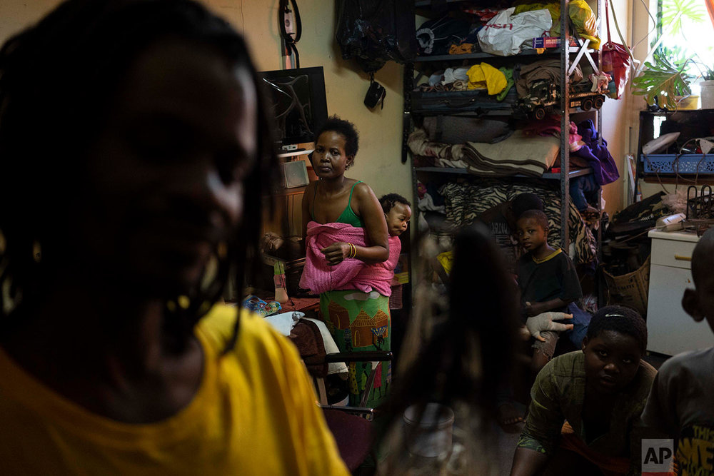In this Tuesday, Oct. 2, 2018 photo, Zimbabwean migrant Kholakele carries her 6-month old baby in her apartment in Johannesburg. (AP Photo/Bram Janssen)