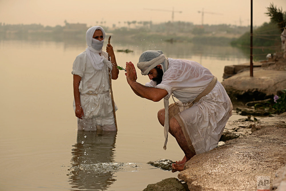 Followers of the ancient Mandaean religious sect perform their rituals along the strip of embankment of the Tigris River reserved for them, in Baghdad, Iraq, on Sunday, Oct. 14, 2018. Mandaeanism follows the teachings of John the Baptist, a saint in both the Christian and Islamic traditions, and their rituals revolve around water. Iraq's soaring water pollution is threatening the religious rites of the tight-knit community, already devastated by 15 years of war. (AP Photo/Hadi Mizban)