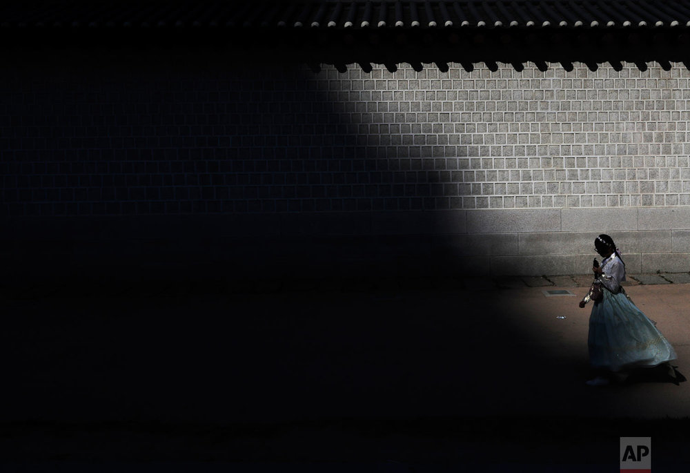 "A visitor dressed in traditional South Korean ""Hanbok"" clothing walks along a wall outside the Gyeongbok Palace, the main royal palace during the Joseon Dynasty and one of South Korea's well known landmarks in Seoul, South Korea, Friday, Oct. 19, 2018. (AP Photo/Lee Jin-man)"