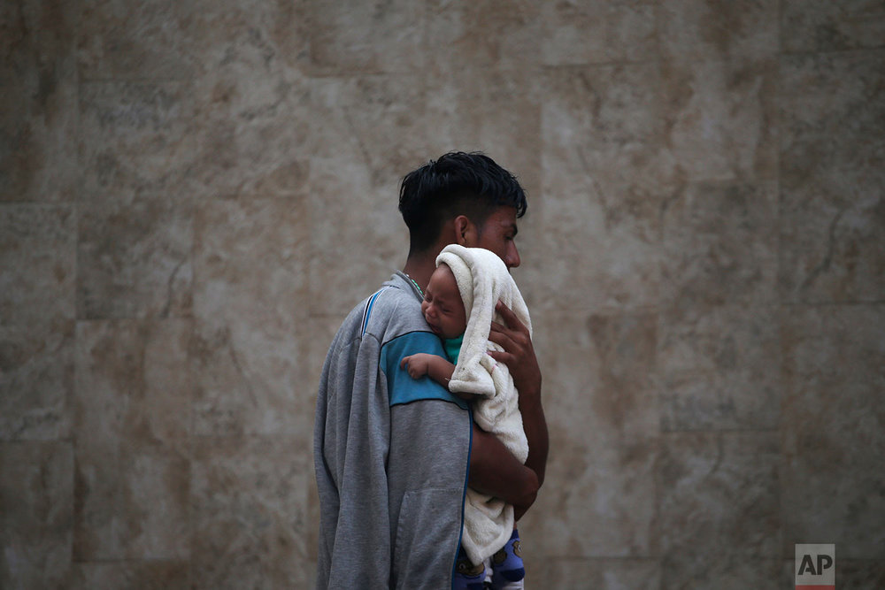 A Central American migrant making their way to the U.S. in a large caravan carries his son after arriving in Tapachula, Mexico, Sunday, Oct. 21, 2018. (AP Photo/Moises Castillo)