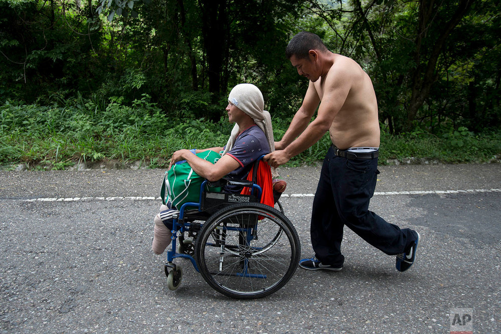 Honduran migrant Omar Orella pushes fellow migrant Nery Maldonado Tejeda in a wheelchair, as they travel with hundreds of other Honduran migrants making their way the U.S., near Chiquimula, Guatemala, Tuesday, Oct. 16, 2018. (AP Photo/Moises Castillo)