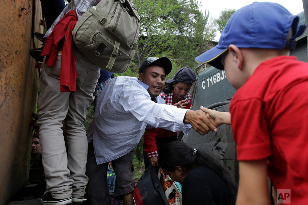 Honduran migrants walking to the U.S. climb on to the space between the cab and bed of a trailer in Zacapa, Guatemala, Wednesday, Oct. 17, 2018. (AP Photo/Moises Castillo)
