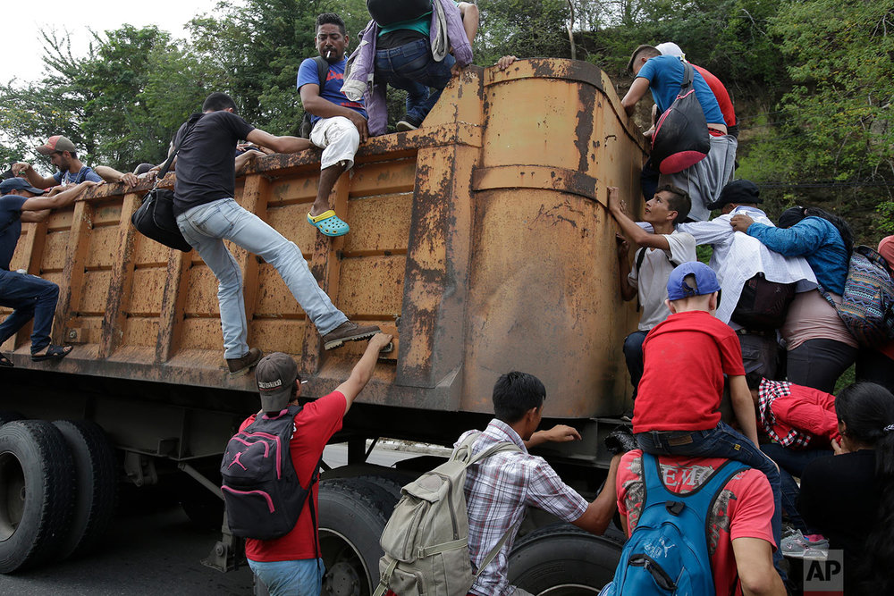 Honduran migrants bound to the U.S border climb into the bed of a truck in Zacapa, Guatemala, Wednesday, Oct. 17, 2018. (AP Photo/Moises Castillo)