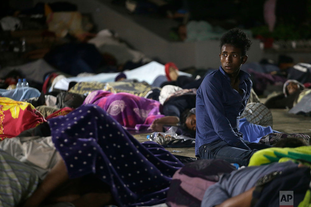 A Central American migrant sits amid a group of sleeping migrants, in Tapachula, Mexico, Monday, Oct. 22, 2018. (AP Photo/Moises Castillo)