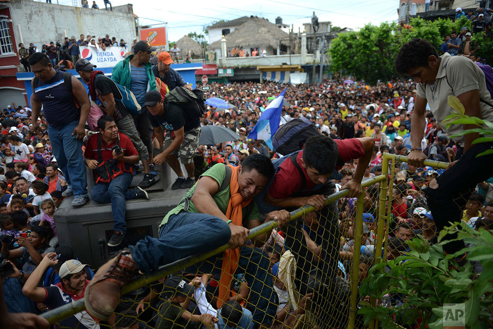 Thousands of Honduran migrants rush across the border towards Mexico, in Tecun Uman, Guatemala, Friday, Oct. 19, 2018. (AP Photo/Oliver de Ros)