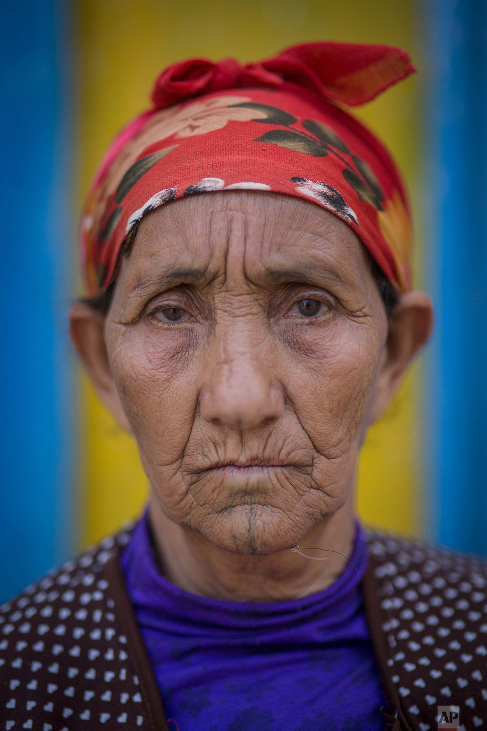 In this Sunday, Oct. 13, 2018 photo, Hadda Saghir, 60, poses for a portrait displaying her face tattoo, in the Middle Atlas town of Tizi N'Isly, near Béni Mellal, central Morocco. (AP Photo/Mosa'ab Elshamy)