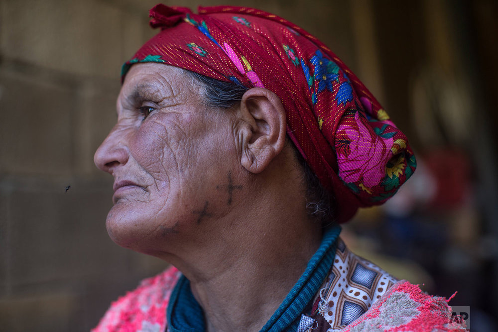 In this Saturday, Oct. 13, 2018 photo, Hano Hamou Youssfi, 65, poses for a portrait displaying her face tattoo, in the Middle Atlas town of Anergui, near Azilal, central Morocco. (AP Photo/Mosa'ab Elshamy)