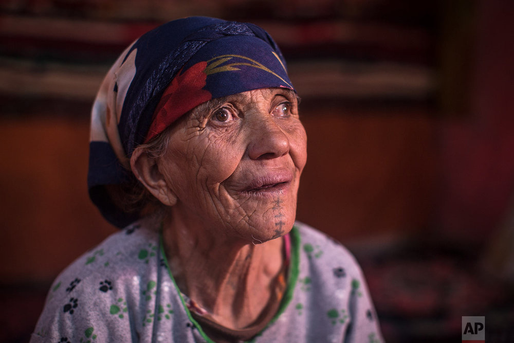 In this Saturday, Oct. 13, 2018 photo, Hadda Oaabjde, 71, poses for a portrait displaying her face tattoo, in the Middle Atlas town of Tinguerf, near Azilal, central Morocco. (AP Photo/Mosa'ab Elshamy)