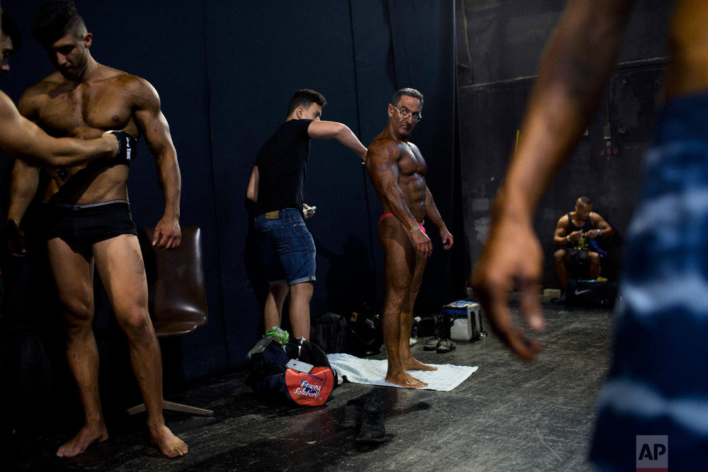 Contestants have their body painted backstage during the National Amateur Body Builders' Association competition in Tel Aviv, Israel on Oct. 18, 2018. (AP Photo/Oded Balilty)
