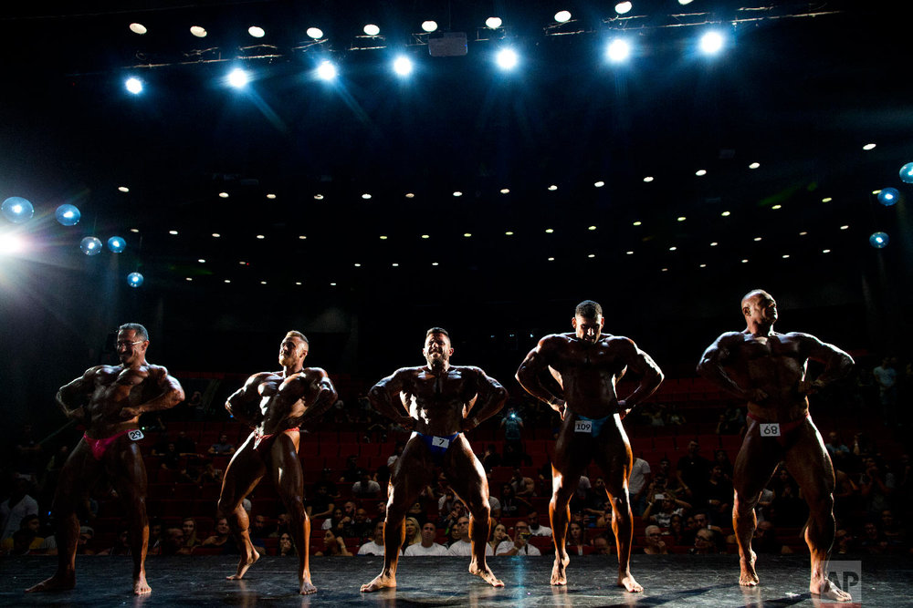 Contestants participate in the final round during the National Amateur Body Builders' Association competition in Tel Aviv, Israel on Oct. 18, 2018. (AP Photo/Oded Balilty)