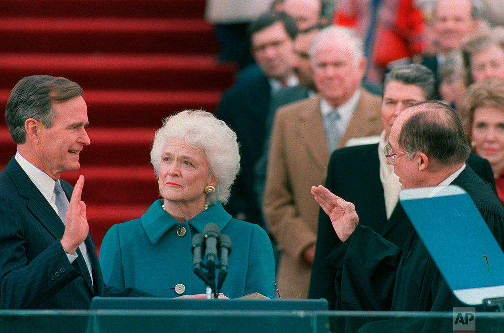 President George H.W. Bush raises his right hand as he is sworn into office as the 41st president of the United States by Chief Justice William Rehnquist outside the west front of the Capitol on Jan. 20, 1989. First lady Barbara Bush holds the bible for her husband. (AP Photo/Bob Daugherty)