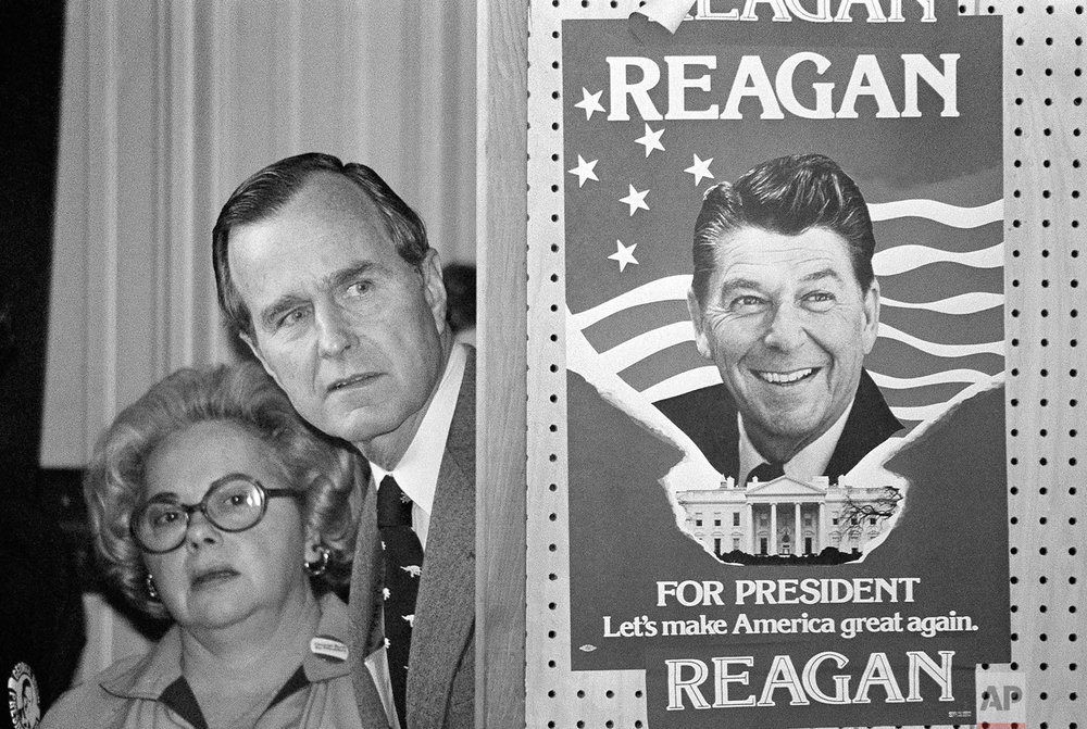 George Bush and an unidentified woman peek around a partition with a poster of Ronald Reagan, one of his opponents for the Republican party presidential nomination, before he speaks on March 4, 1980, in Columbia, S.C. (AP Photo)