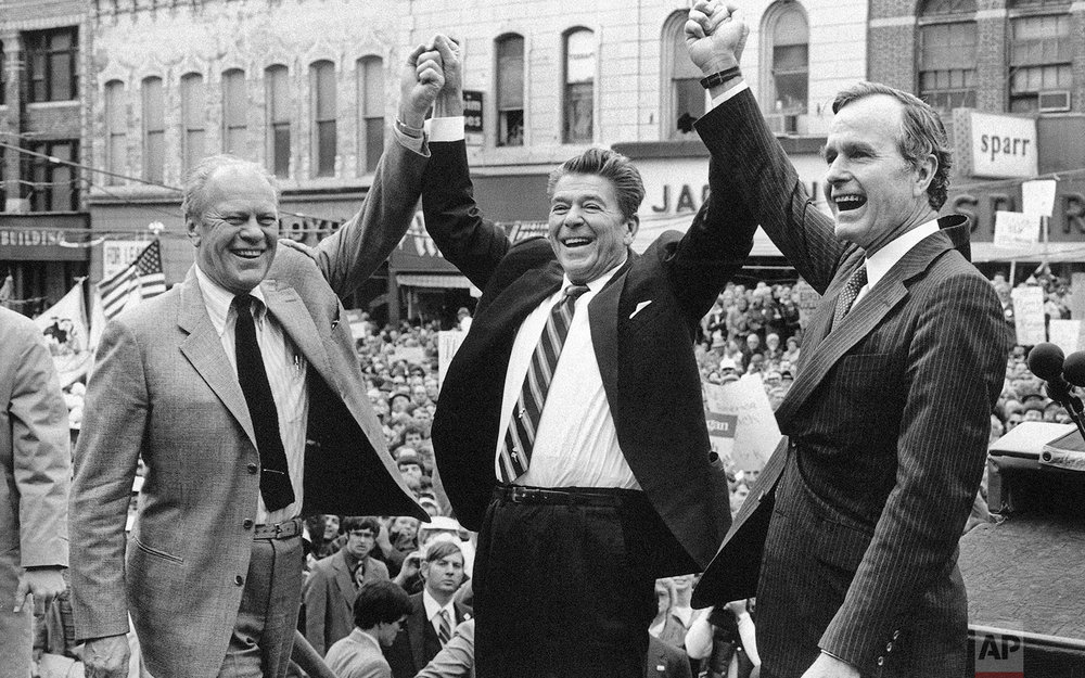 Former President Gerald Ford lends his support to Republican presidential candidate Ronald Reagan and his running mate George H.W. Bush, on Nov. 3, 1980, in Peoria, Ill. (AP Photo)
