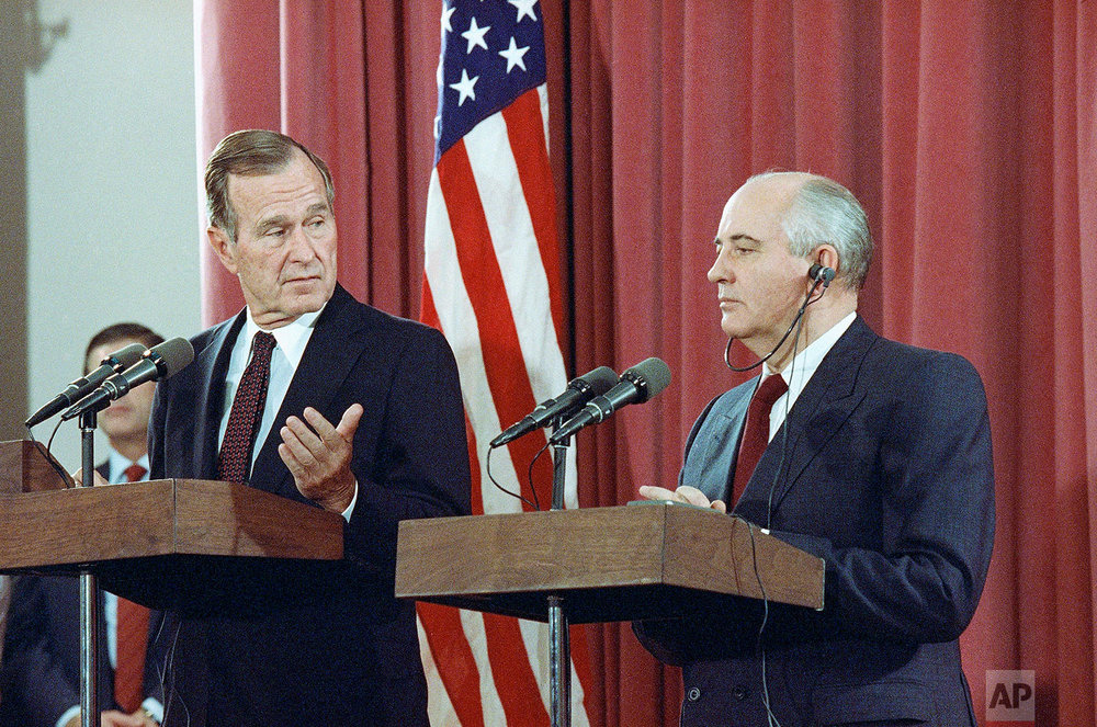 U.S. President George H. Bush gestures during a joint news conference with Soviet President Mikhail Gorbachev, on Oct. 29, 1991, at the Soviet Embassy in Madrid. (AP Photo/Jerome Delay)