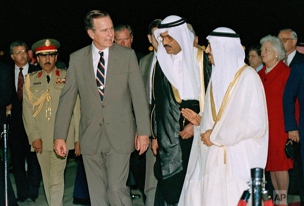 President George Bush is greeted by King Fahd as he arrives in Saudi Arabia, Nov. 21, 1990. At right is first lady Barbara Bush. At center is an interpreter. (AP Photo/J. Scott Applewhite)