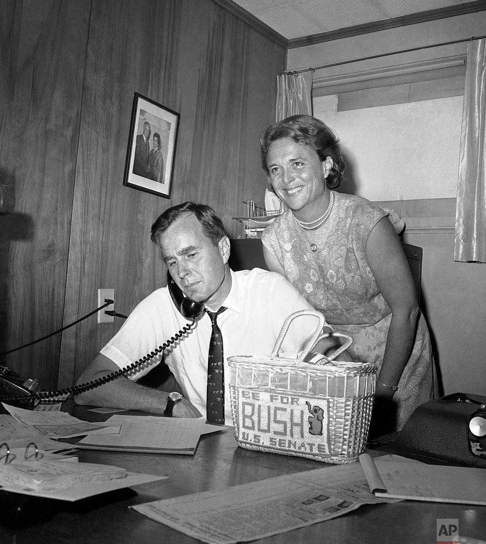George Bush, candidate for the Republican nomination for the U.S. Senate, gets returns by phone at his headquarters in Houston, Saturday, June 6, 1964, as his wife Barbara smiles at the news. (AP Photo/Ed Kolenovsky)