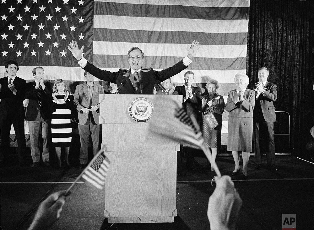 Flag-wavers greet Vice President George Bush after he was re-elected to the post of vice president, Nov. 7, 1984, in Houston, Texas. The vice president's wife Barbara Bush is seen second from right. Others are unidentified. (AP Photo/F. Carter Smith)