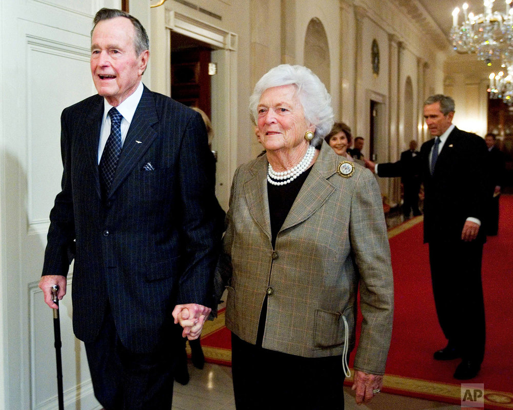 Former President George H. W. Bush, left, walks with his wife, former first lady Barbara Bush, followed by their son, President George W. Bush, and his wife first lady Laura Bush, to a reception in honor of the Points of Light Institute, Wednesday, Jan. 7, 2009, in the East Room at the White House in Washington. (AP Photo/Manuel Balce Ceneta)