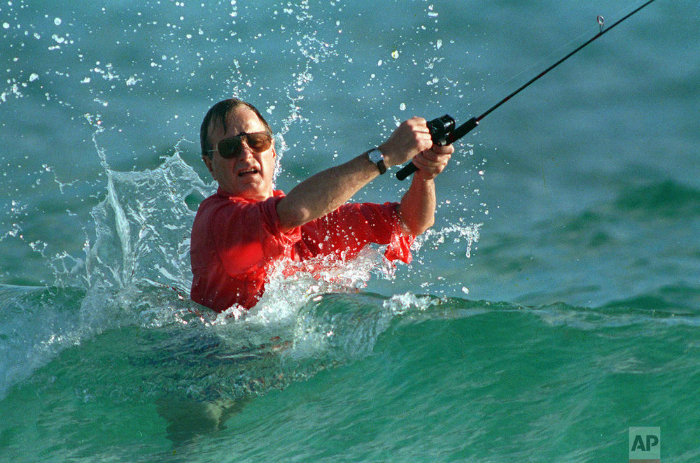 Waves splash President-elect George Bush as he casts a line while fishing in Gulf Stream, Fla., on Nov. 12, 1988. (AP Photo/Kathy Willens)