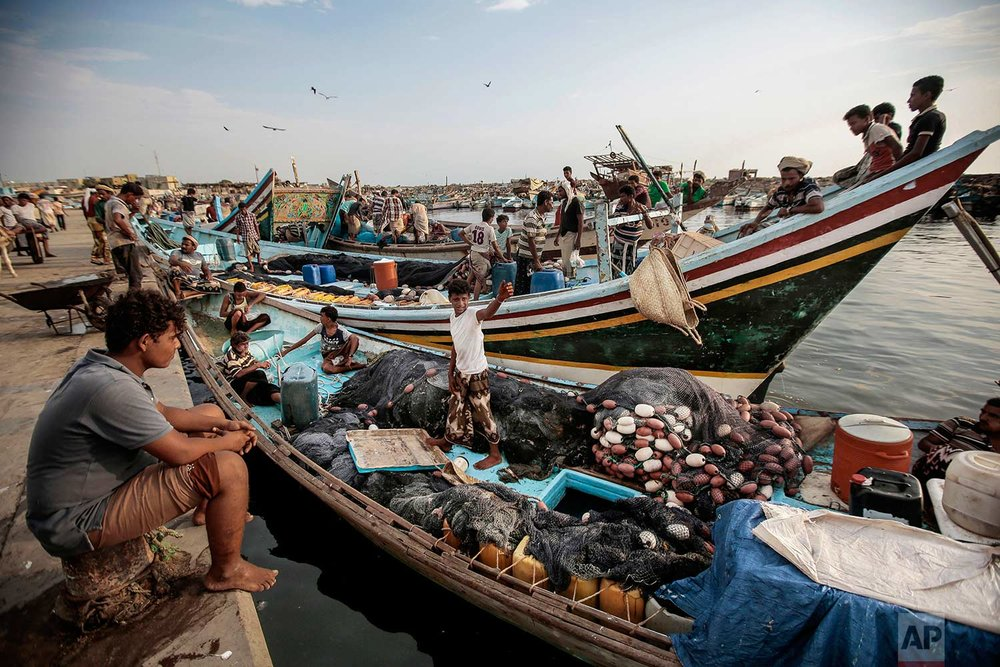 In this Sept. 29, 2018, photo, fishermen rest on their boats before fishing at the main fishing port, in Hodeida, Yemen. (AP Photo/Hani Mohammed)