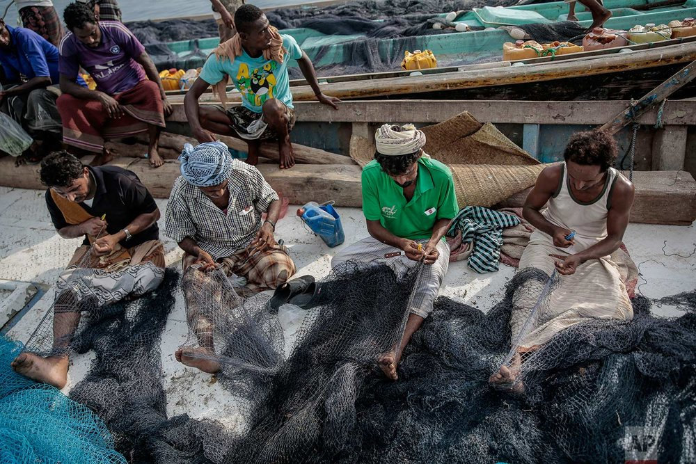 In this Sept. 29, 2018, photo, Yemeni fishermen fix their nets before a fishing trip at the main fishing port, in Hodeida, Yemen. (AP Photo/Hani Mohammed)