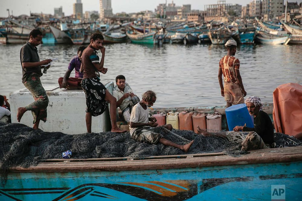 In this Sept. 29, 2018, photo, 71 year-old Yemeni fisherman Ammar Ahmed, center, prepares his net before a fishing trip at the main fishing port, in Hodeida, Yemen. (AP Photo/Hani Mohammed)