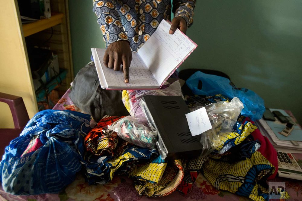 Toussain Kanyimb Nawej shows goods left as collateral by patients unable to pay their bills at the Katuba Reference Hospital in Lubumbashi, Democratic Republic of the Congo on Wednesday, Aug. 15, 2018. Hospital data obtained by The Associated Press in Congo suggest imprisonment is common in both public and private facilities, including those that receive free drugs for AIDS, malaria and reproductive health care from U.S. partners including Columbia University in New York, USAID, and the U.S. President's Emergency Plan for AIDS Relief, or PEPFAR. (AP Photo/Jerome Delay)