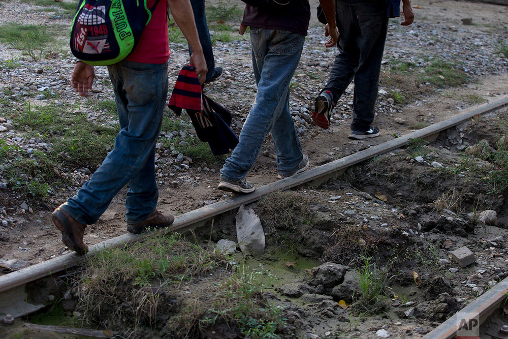A small group of Honduran migrants trying to reach the U.S. border walk along train tracks in Trancas Viejas, Veracruz state, Wednesday, Oct. 24, 2018. (AP Photo/Rebecca Blackwell)