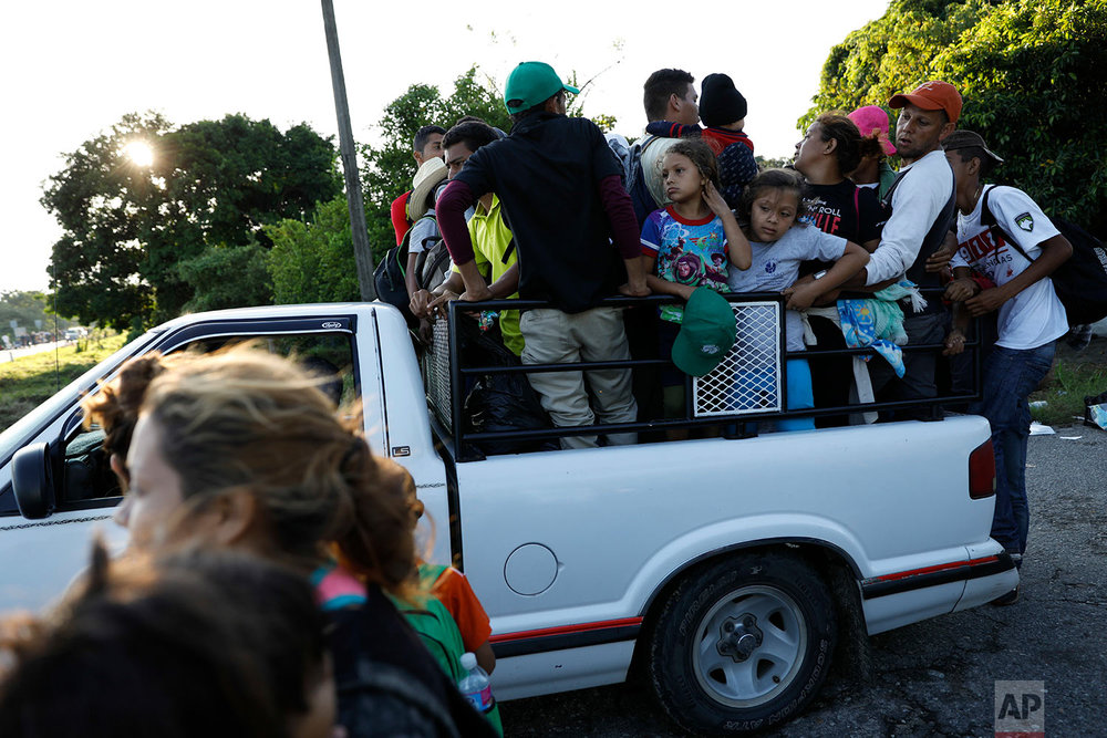 Central American migrants hitch a ride, as a thousands strong caravan heads north hoping to reach the U.S. border, near Mapastepec, Mexico, Thursday, Oct. 25, 2018. (AP Photo/Rebecca Blackwell)