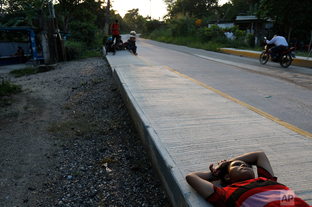 Liseth Lopez, 23, from Comayagua, Honduras, rests on a sidewalk as she travels with a half dozen Honduran friends trying to reach the U.S. border, in Trancas Viejas, Veracruz state, Wednesday, Oct. 24, 2018. (AP Photo/Rebecca Blackwell)
