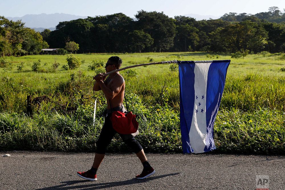 A Honduran migrant carries his national flag as he walks north as part of a thousands strong caravan trying to reach the U.S., still over 1000 miles away, near Mapastepec, Mexico, Thursday, Oct. 25, 2018. (AP Photo/Rebecca Blackwell)