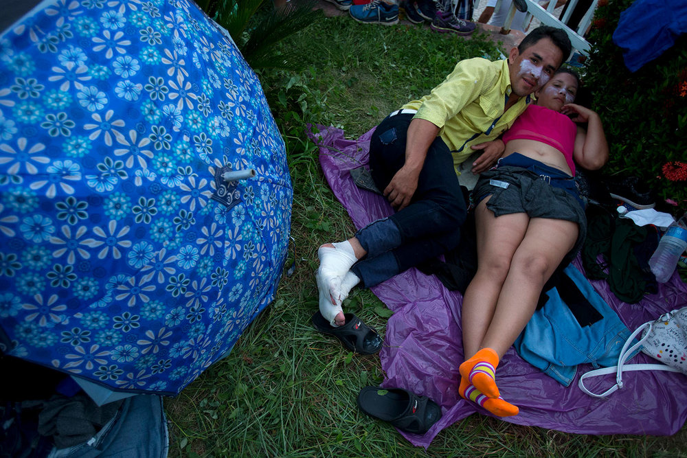 A Honduran couple, who received medical treatment for burned faces and his injured feet, rest together as a thousands-strong caravan of Central American migrants stops for the night in Pijijiapan, Chiapas state, Mexico, on their way toward the U.S. border, Thursday, Oct. 25, 2018. (AP Photo/Rebecca Blackwell)