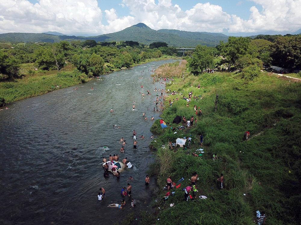 Honduran migrants take a bath in a river in Pijijiapan, Mexico, Thursday, Oct. 25, 2018. (AP Photo/Rodrigo Abd)