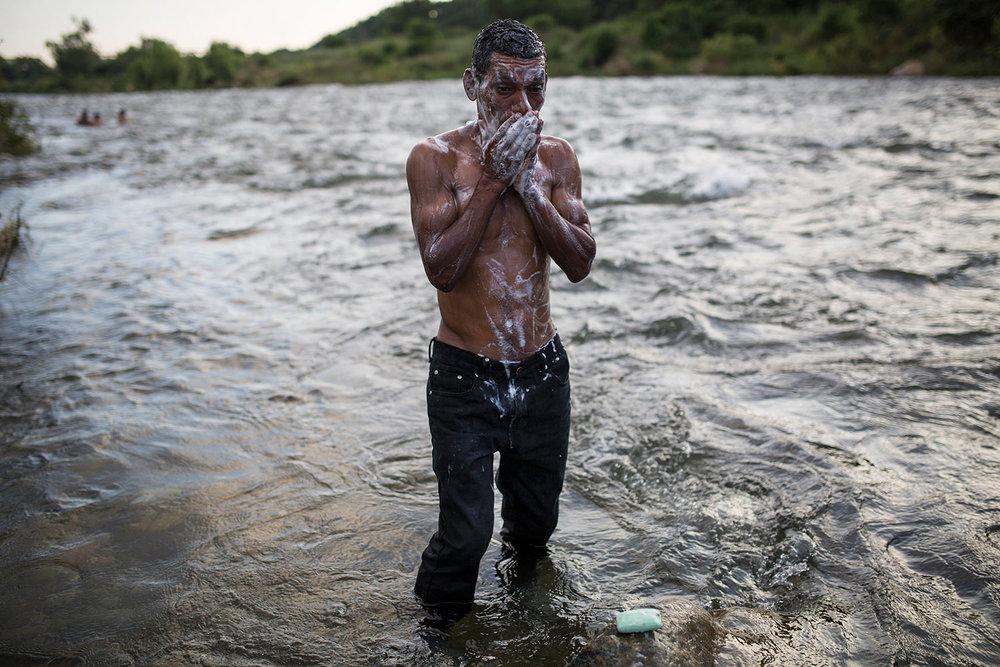 A Honduran migrant takes a bath in a river in Pijijiapan, Mexico, Thursday, Oct. 25, 2018. (AP Photo/Rodrigo Abd)