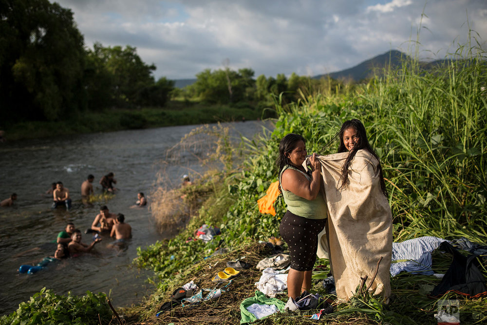 Honduran migrant Malcy Gonzales gets dressed with the help of a friend after having a bath in a river in Pijijiapan, Mexico, Thursday, Oct. 25, 2018. (AP Photo/Rodrigo Abd)