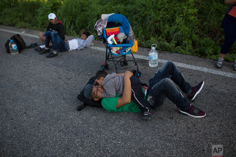 Central American migrants Santiago Mardoqueo, 19, plays with his son Carlos, 2, take a break as they make their way to Pijijiapan, Mexico, Thursday, Oct. 25, 2018. (AP Photo/Rodrigo Abd)