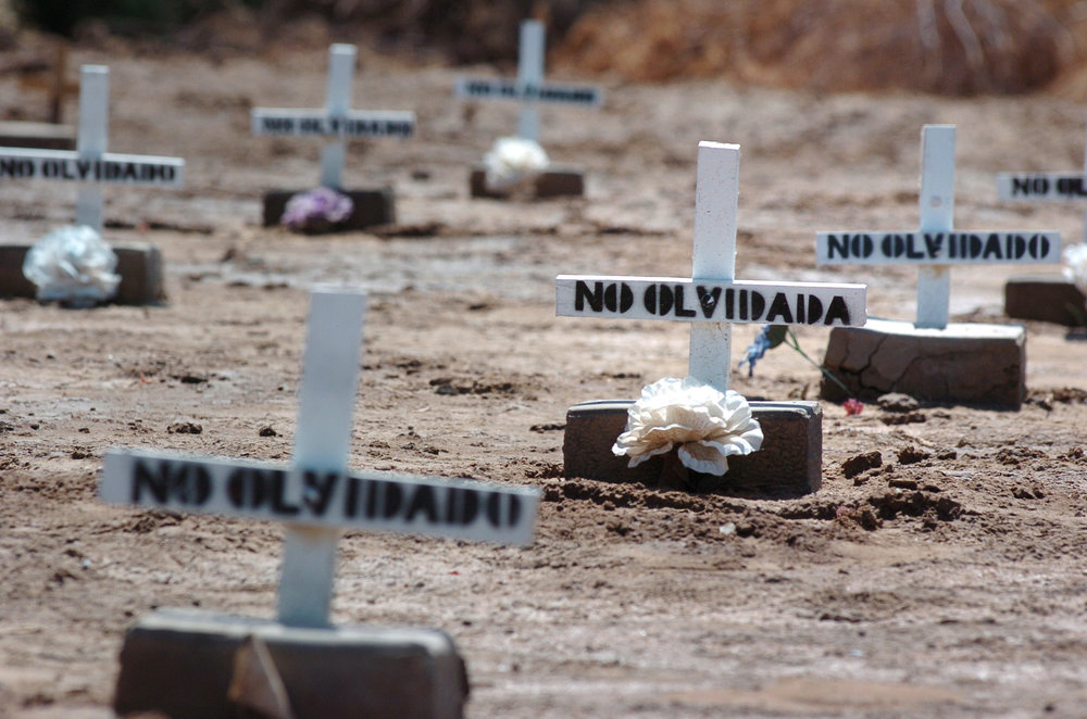 In this Thursday, May 16, 2006 photo, white crosses and cement bricks mark the graves where unidentified migrants who died while crossing the U.S.-Mexico border are buried in a public cemetery in Holtville, California. (AP Photo/David Muang)