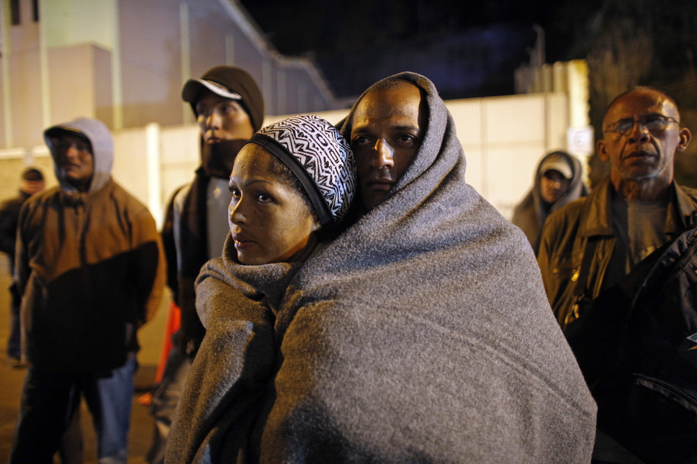 In this Sunday, Aug. 5, 2018 photo, Venezuelan migrants cover themselves with blankets as they wait in the cold for a lift after crossing the border from Colombia on their way to Peru in Rumichaca, Ecuador. (AP Photo/Ariana Cubillos)