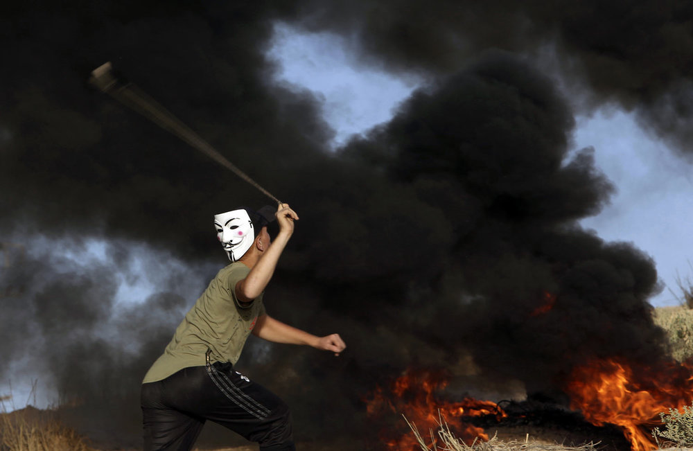 A protester wearing a Guy Fawkes mask hurls stones at Israeli troops while others burn tires near the fence of the Gaza Strip border with Israel during a protest on the beach near Beit Lahiya, northern Gaza Strip on Monday, Oct. 29, 2018. Thousands gathered Monday on the beach for a Hamas-led protest against the blockade. The Gaza Health Ministry says a 27-year-old Palestinian was shot dead during the protest. (AP Photo/Adel Hana)